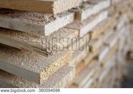 Stack Of Natural Rough Wooden Boards Close-up. Storage Of Wood In A Carpenters Workshop Or At A Sawm