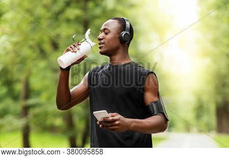 African Jogger Drinking Water And Using Smartphone, Resting While Training At Park, Copy Space