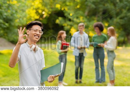 Happy Chinese Student Guy Gesturing Ok While Posing Outdoors At Campus With Group Of His Classmates