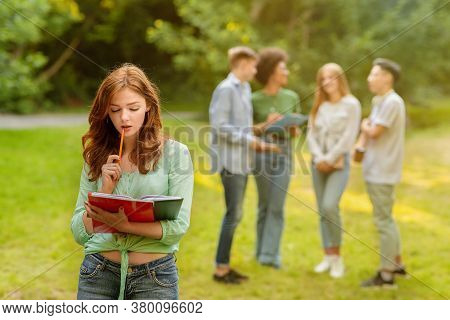 Education First. Student Girl Preparing For Exam Outdoor While Her Classmates Chatting On Background