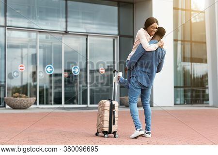 Family Reunion. Happy Black Couple Meeting At Airport After Arrival, Loving Man Lifting Wife In Air,