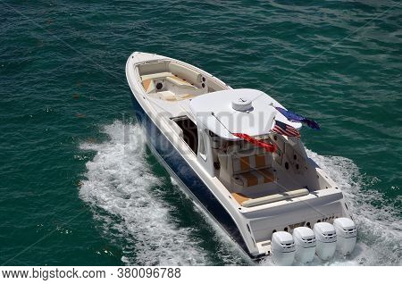 Angled Overhead View Of A High-end Speedboat Powered By Four Outboard Engines.