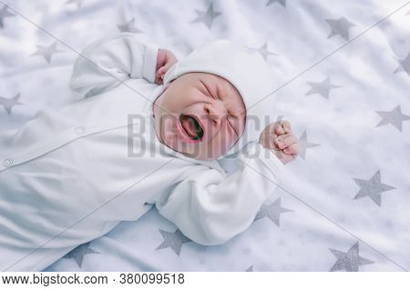 Newborn Baby Is Lying In A Crib, Screaming And Crying, Tired And Hungry