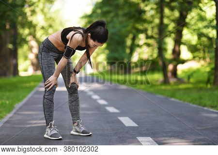 Taking Breath. Exhausted Asian Jogger Girl Resting After Running On Path In Park, Free Space