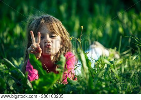 Little cute girl posing for a photo in the green grass.