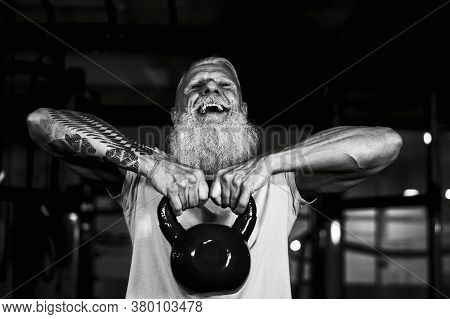 Senior Fitness Man Doing Kettle Bell Exercises Inside Gym - Fit Mature Male Training In Wellness Clu