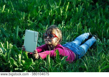 Little funny girl makes a selfie on a tablet in the green grass.