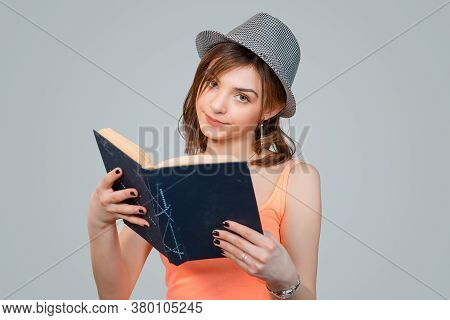 Skeptical Woman Holding Black Book Looking At You Camera Skeptically, Teenage Hipster Girl In Gray H