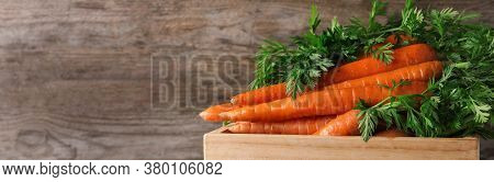 Crate Of Fresh Carrots On Wooden Background, Closeup With Space For Text. Banner Design