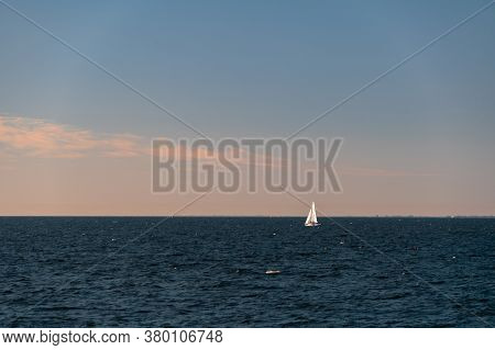 White Sailboat On A Calm Sea Or Ocean During Sunset. Large Copy Space. Minimalistic Style.
