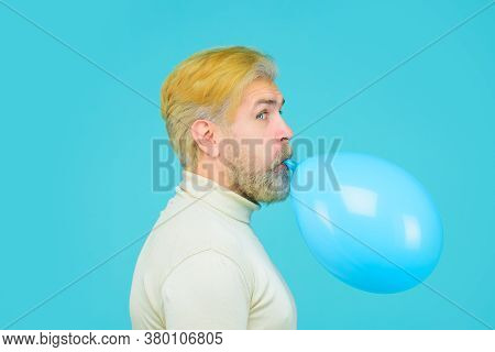 Happy Birthday. Preparation To Party. Attractive Man Is Blowing Blue Balloon. Stylish Man Inflating