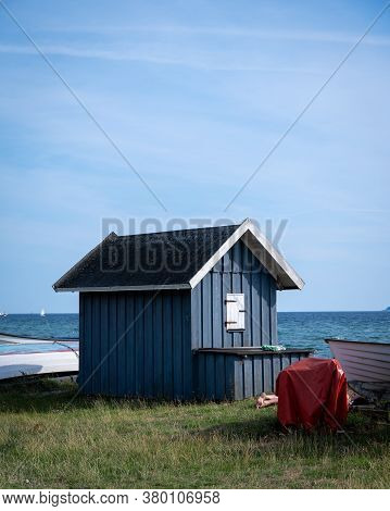 A Blue Closed Wooden Fishing Hut Next To Some Boats Just By The Beach In Southern Sweden