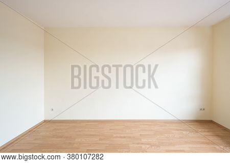 Empty Room In An Apartment With Light Walls And Wood Decor Laminate On The Floor, Concept For Housin