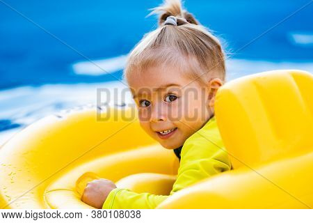 Child In Swiming Pool In Yellow Inflatable Waist Baby Swim Float On Summer Day. Children In Swimming