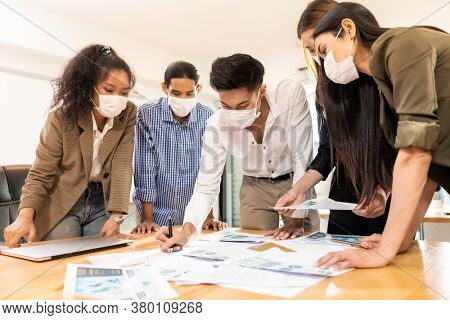 Interracial asian business team brainstorming idea at office meeting room after reopen due to coronavirus COVID-19 city lockdown. They wear face mask reduce risk to infection as new normal lifestyle.