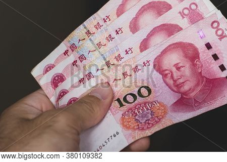 Persons Hand Giving The Currency Of The China - One Red Hundred Renminbi Or Yuan Notes Spread Out On