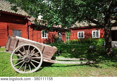 Vasteras, Sweden - Jul 03, 2019: Vallby open-air Museum. Old wooden cart on big wheels on green grass in yard surrounded by Swedish traditional red houses. Summer sunny day