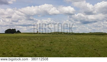 Lone Silo Among The Clouds And Grass Of A Midwest Farm