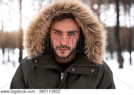 Handsome Serious Brutal Bearded Young Caucasian Man Standing Outdoors Fur Hood In Winter Season Fore