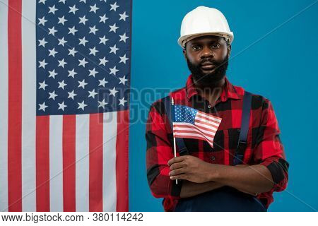 Young bearded African-american worker in flannel and hardhat holding flag while standing against stars-and-stripes and blue background