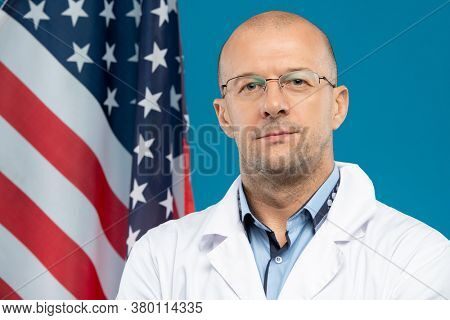 Middle aged bald clinician in eyeglasses and whitecoat looking at you while standing against stars-and-stripes flag in front of camera