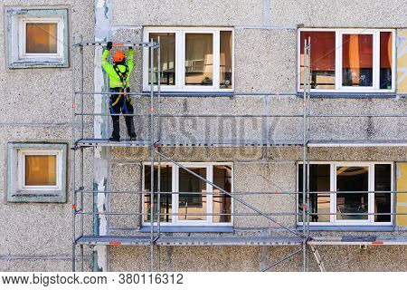 The Worker Assembles The Scaffolding On The Facade Of A Multi-storey House At A Dangerous Height