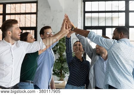 Overjoyed Successful Diverse Employees Giving High Five At Meeting