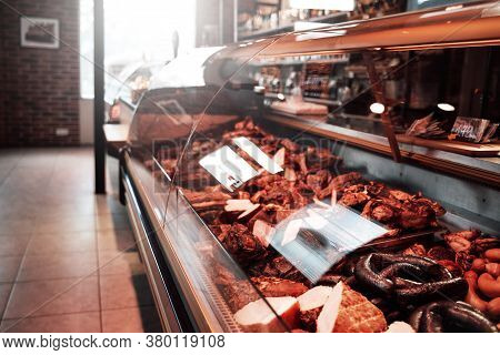 Huge Assortment Of Meat Selection. A Shop With A Row Of Stalls Full Of Meat. Butcher Shop Inside.