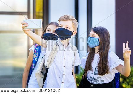 School Children Wearing Protective Face Masks Taking Selfie At School Reopening - New Normal Concept