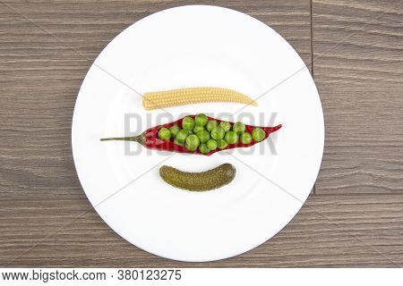 Salad Of Pickled And Pickled Corn, Peas, Cucumber And Red Pepper On A White Plate.  Food And Vegetab