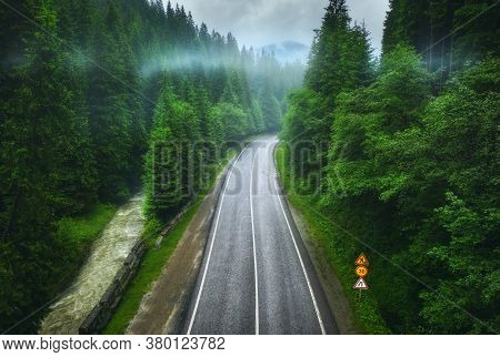 Aerial View Of Road In Beautiful Green Forest In Low Clouds In Rainy Summer Day. Colorful Landscape