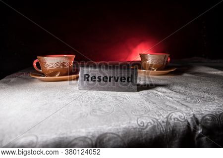 Reserved Sign On The Table. A Tag Of Reservation Placed On The Wood Table. Metal Tag With Reservatio