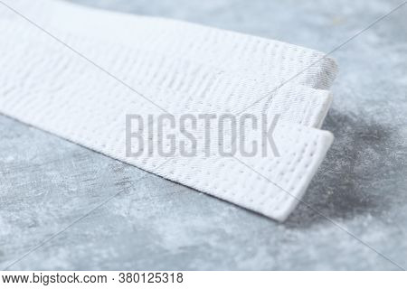 White Karate Belt On Rustic Wooden Background. Close Up. Copy Space.