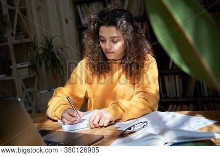 Hispanic Teen Girl College Student Study From Home Office Making Notes Doing Homework In Sunny Room.