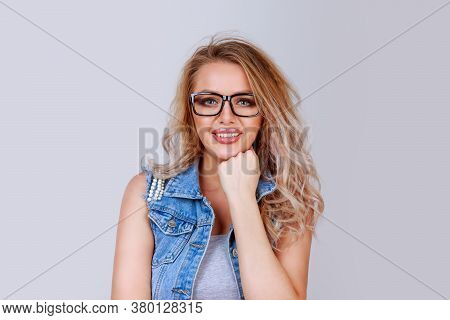 Pretty Young Smiling Blonde Woman In Glasses And Denim Waistcoat Leaning On Hand And Looking At Came