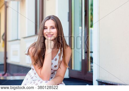 Portrait Of Cheerful Young Woman Sitting Outdoors And Smiling. Beautiful Young Girl In White Dress W