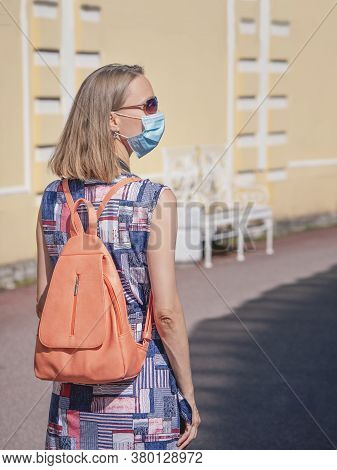 Female Tourist In A Medical Mask With A Backpack On The Street. Safety In A Public Place While Epide