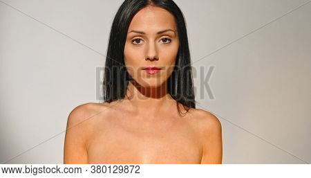 Front view of natural looking woman with dark hair smiling to camera.