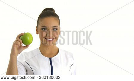 Nurse or young doctor holding an apple smiling. Health care concept.