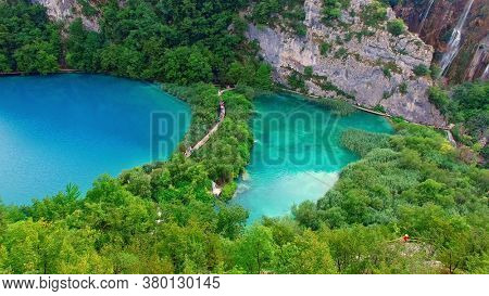 The National Park of Plivice Lakes in mountain Krast in Croatia. The aerial view of board walk on waterfall cascade of Plitvice Lakes, the UNESCO World Heritage. Travel destination for turists.