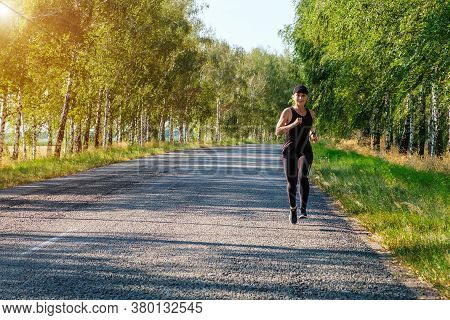 Young White Fitness Woman Runs On Country Road, Front View. Workout, Fitness, Marathon Concept. Copy