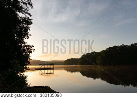 A Dock On A Lake Surrounded By Trees On A Foggy Morning At Sunrise; Landscape