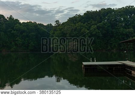 The Swim Platform On A Dock At Dawn With A Ladder Leading Into The Water Surrounded By Trees And The