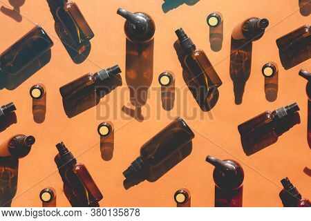 Set Of Reusable Glass Bottles For Face Cosmetics On Shadow Background. Top Horizontal View Abstract