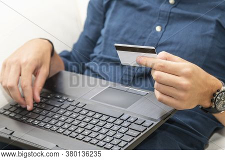 Close Up Of A Man Holding A Credit Card While Using A Laptop