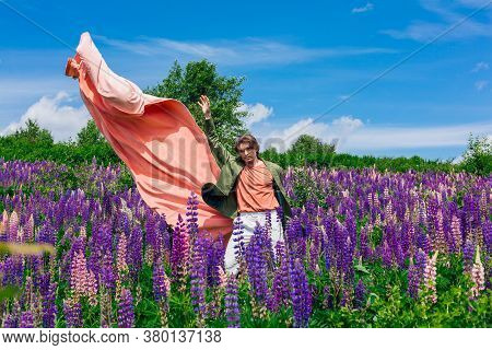 Tall Handsome Man Standing On Lupine Flowers Field With Flying Pink Cloth