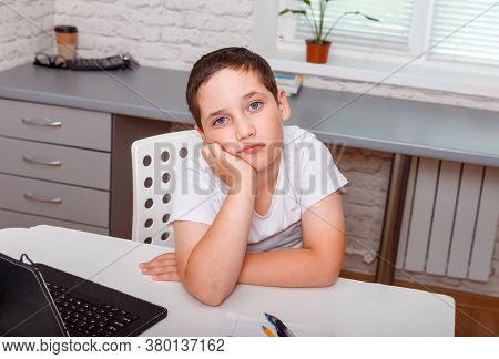 Sad Schoolboy Sitting Alone At Desk At Home. Grumpy Dissatisfied Boy. Portrait Of An Upset Cute Boy.