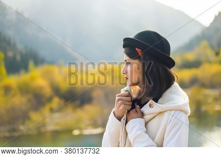 A Young Woman In A White Coat Walking In Nature, Looks Away. Take Cover From The Autumn Cold.