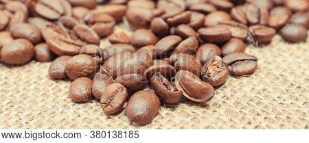 Heap Of Roasted Coffee Grains On Old Jute Burlap