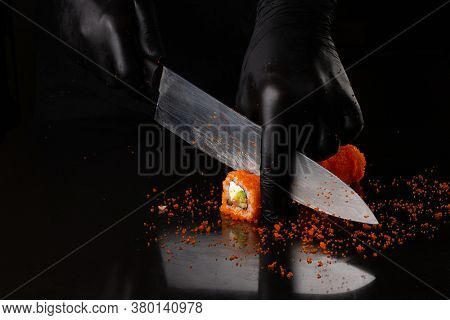Process of cutting California roll sushi with red masago caviar by hand in black gloves with knife on black background